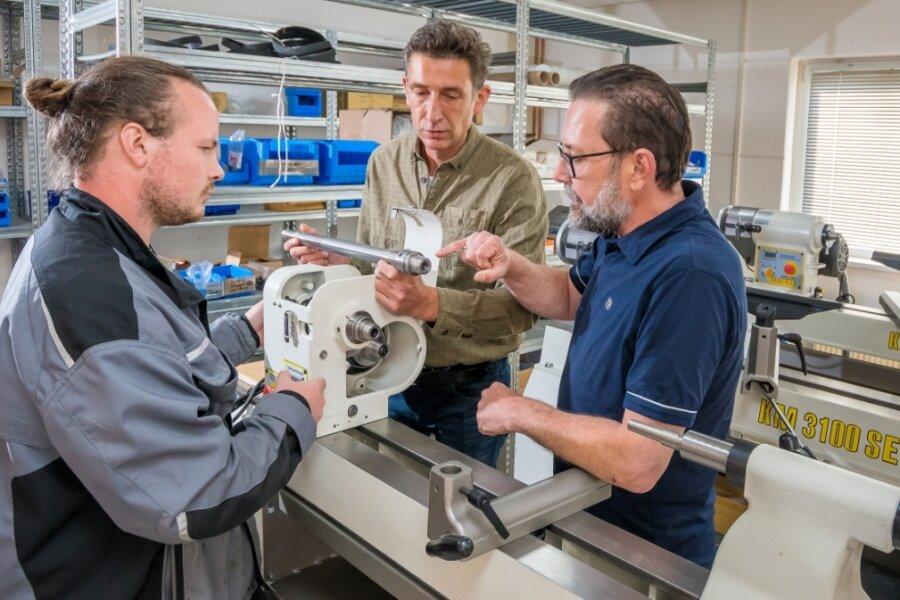 Robin Leonhardt bespricht mit Roland und Martin Steinert (v. l.) bei der Montage einer Drechselbank ein technisches Detail.