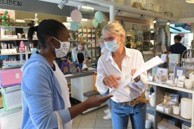 """Bei Schreibwaren Steyer am Freiberger Obermarkt berät Inhaberin Anke Krause (r.), zugleich Chefin des Gewerbevereins, gerade eine Kundin. """"Das Tragen der Maske ist notwendig, aber auch anstrengend"""", sagt Krause. """"Die Kunden sehen unser Lächeln nicht. Und auch wir können die Reaktion unserer Kunden nicht sehen."""""""