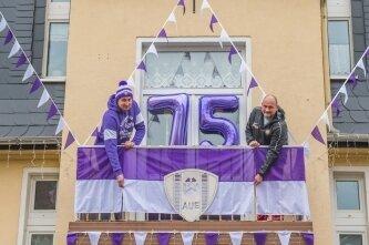 """Vier Stunden haben Oliver Litschko (l.) und sein Schwiegervater Andreas Pahlow gebraucht, um ihr Haus an der Schneeberger Straße in Aue am Wochenende mit FCE-Utensilien zu schmücken. Angebracht wurden zwei Schals und Sitzkissen an den Fenstern, drei Fahnen mit einer 24 Meter langen Wimpelkette und zwei Luftballons mit der Zahl """"75"""". Oliver Litschko sagt: """"Es war sehr schwierig, eine lila-weiße Wimpelkette zu bekommen. Im Internet sind wir schließlich nach langer Suche fündig geworden."""""""