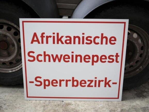 Ein Schild mit der Aufschrift «Afrikanische Schweinepest - Sperrbezirk» steht in einem Zentrallager für Tierseuchenbekämpfungsmaterial (Archiv). Die ASPhat Deutschland erreicht.