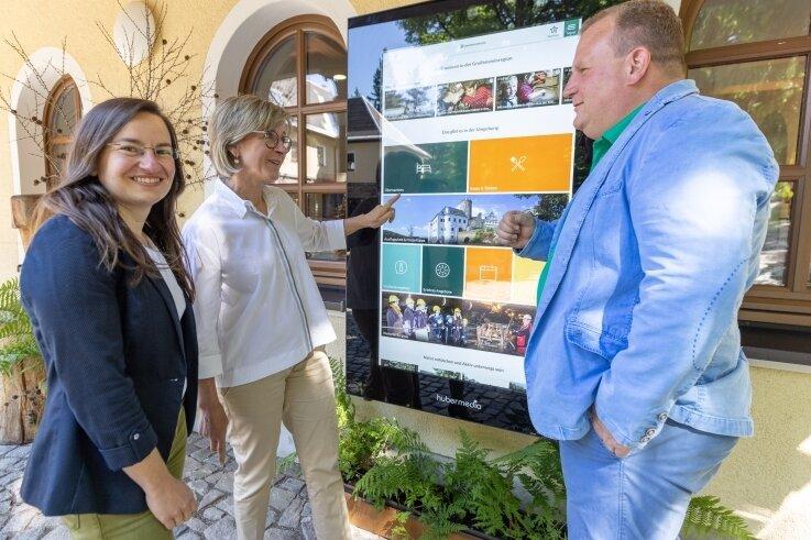 Tourismuskoordinatorin Corinna Bergelt (links) testet mit Ehrenfriedersdorfs Bürgermeisterin Silke Franzl und Gelenaus Bürgermeister Knut Schreiter das neue Informationsterminal der Greifensteinregion.