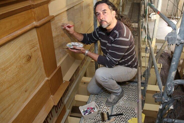 Hoch oben in der Kirche Sosa ist Restaurator Holger Blauhut dabei, das Holz der Empore zu erneuern. Was wie Eiche und Vogelaugenahorn aussieht, sind in Wirklichkeit geschickt aufgetragene Muster.