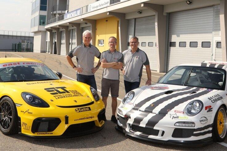 """Den gelben Porsche Cayenne GT4 werden Uwe Wächtler und Steve Kirsch (von links) beim Rennen der NES 500 an den Start bringen. Ruben Zeltner fährt mit dem """"brüllenden Zebra"""", Baujahr 2012, im Rennen der Porsche Club Historic Challenge."""