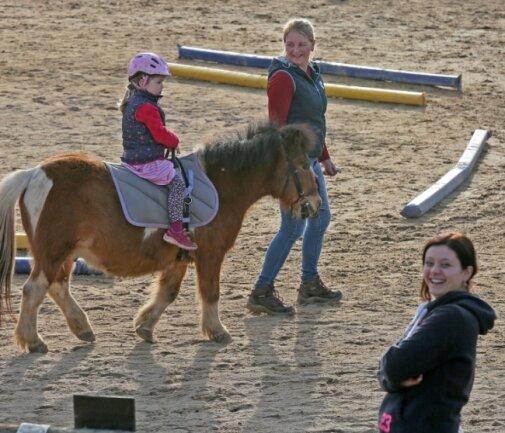 """Die Tiere müssen von den Pferdebesitzern selbst bewegt werden. Nadine Unger führt ihr Pony, auf dem Alina Kunick am """"Glück der Erde"""" schnuppern darf. Mutter Janine Kunick hat offensichtlich Spaß dabei."""