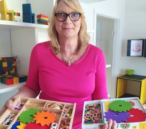 Barbara Seidler zeigt das neue Schmuckstein-Mandala. Die große Ausführung ist für Kindergärten, die kleine für zuhause.