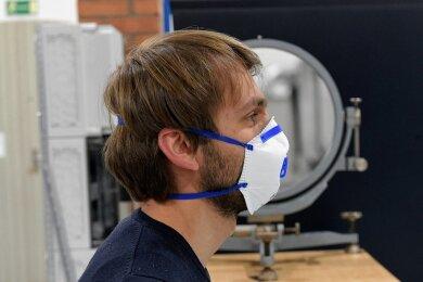 Versuchshalle A der Professur für Strömungsmechanik und Strömungsmaschinen in Freiberg: Mitarbeiter Emanuel Thom spricht durch eine Maske. Der Schlierenspiegel im Hintergrund bündelt LED-Lichtstrahlen, reflektiert sie und macht so die Aerosole sichtbar.