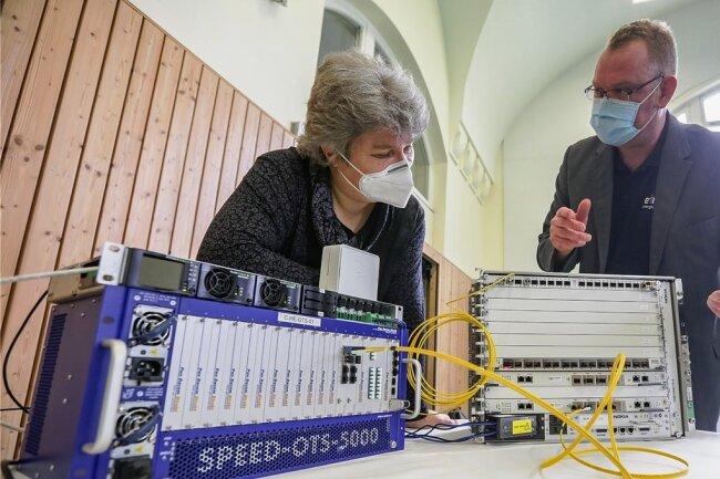 Die Schulleiterin der Grundschule Rabenstein, Katrin Jechorek und Patrick May von Eins Energie schauen sich Technik an: Diese neue Verteilstation versorgt Haushalte mit schnellem Internet aus Glasfaser-Kabeln.