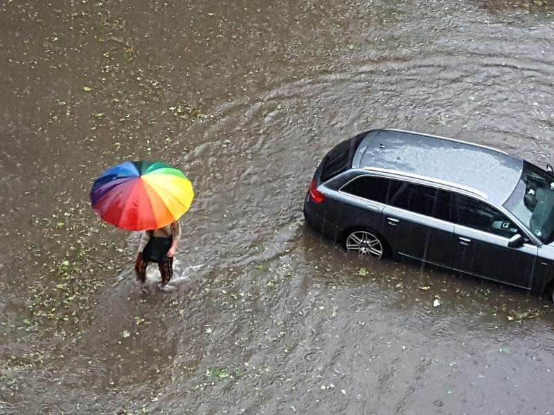 Ein Passant läuft in Wuppertal durch eine nach heftigen Regenfälle überflutete Straße.