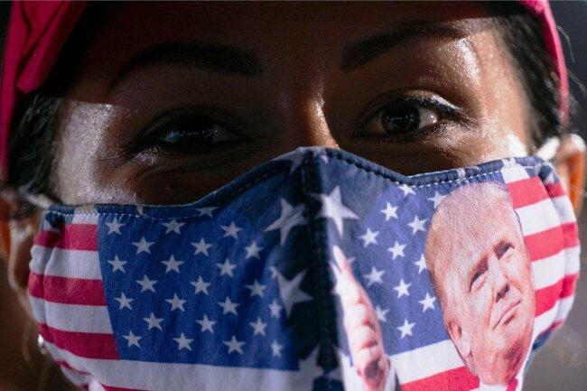 Eine Unterstützerin von US-Präsident Donald Trump verfolgt dessen Rede auf einer Wahlkampfkundgebung in Opa-Locka im US-Bundesstaat Florida .