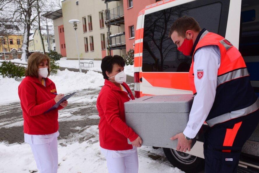 David Lehr vom Malteser-Hilfsdienst (rechts) lädt mit Ramona Richter (links) und Angela Steidl vom ASB-Altenpflegeheim eine Kiste mit Impfdosen ab. Am Donnerstag sind 150 Personen geimpft worden.