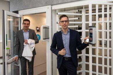 Die beiden Kemas-Geschäftsführer Volker Rattmann (links) und Björn Grämer demonstrieren die Funktionsweise einer automatischen Übergabestation für Krankenhauskleidung.