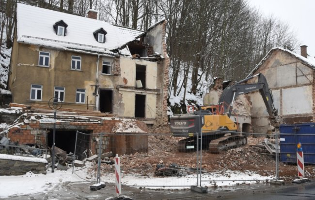 Der Bagger hat sich weit vorgefressen: Die Gebäude Elsterstraße 12 und 14 an der B 92 in Adorf werden abgetragen. Der Verkehr auf der Bundesstraße wird seit Montag wechselseitig per Ampel vorbeigeleitet.