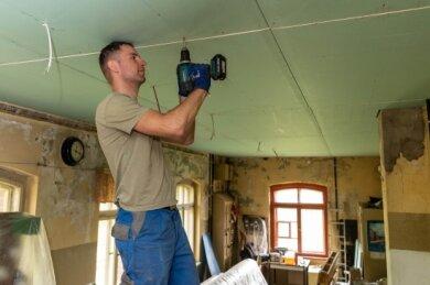 Im Inneren des Gebäudes gibt es immer wieder etwas zu tun. Rico Bernhardt befestigt an der Decke Trockenbauplatten.