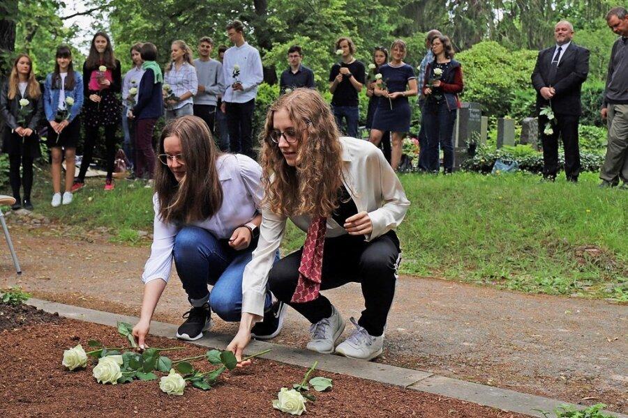 Zum Gedenken an den ehemaligen Schulleiter legen die Schüler Blumen an seiner Grabstelle nieder.