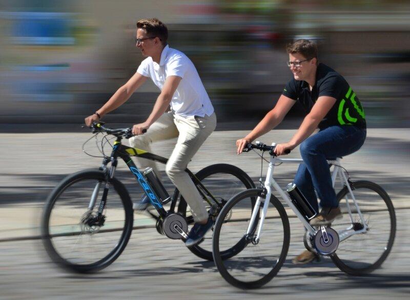 Die Geschäftsführer der Firma Pendix Christian Hennig (links) und Thomas Herzog fahren in der Zwickauer Innenstadt auf Fahrrädern, die sie mit ihrem eigenen Nachrüstsystem zu E-Bikes gemacht haben.