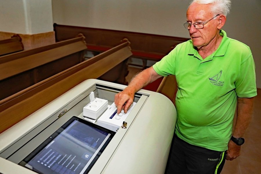Wolfgang Dietrich vom Kirchenvorstand macht sich mit der neuen Technik vertraut. An dem Bedienpult können per Touchscreen auch die Kirchenglocken geläutet werden.