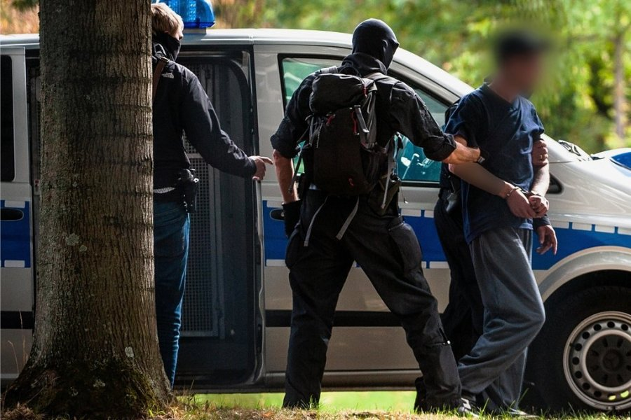 Am Montag vor dem Bundesgerichtshof in Karlsruhe: Einer der mutmaßlichen Rechtsterroristen aus der Chemnitzer Szene, die am Morgen in Bayern und Sachsen festgenommen wurden, wird von Polizisten abgeführt.