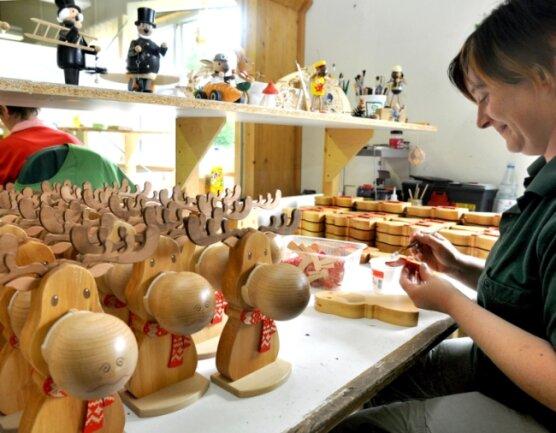 """<p class=""""artikelinhalt"""">Neu bei der Drechslerei Kuhnert in Rothenkirchen werden die Elche aus Massivholz - es sind Brillenständer - produziert. Nadine Schmalfuß klebt ihnen den Schal an. </p>"""