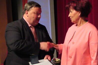 Oberbürgermeister Sören Kristensen überreicht Angelika Schunck die Ehrenmedaille.