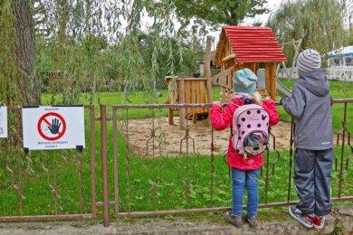 """Bisher sind die Kinder im wahrsten Sinne des Wortes nur Zaungäste am Spielplatz neben der """"Parkschänke"""". Erst nach dem Bau der neuen Umzäunung und der Abnahme durch den Tüv dürfen sie ihn nutzen."""