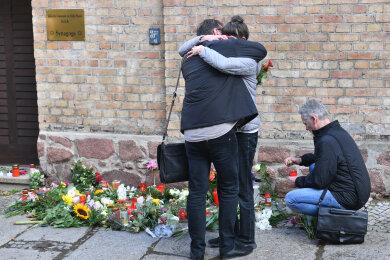 Menschen trauern vor Kerzen und Blumen an der Synagoge.