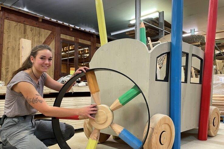 """Lisa Lang, Lehrling im zweiten Lehrjahr bei Massivholz Design, ist federführend bei der Umsetzung des Projekts """"Bauernhof"""" für Waschleithe. Im Bild zeigt die junge Frau aus Annaberg den """"Traktorreifen."""""""