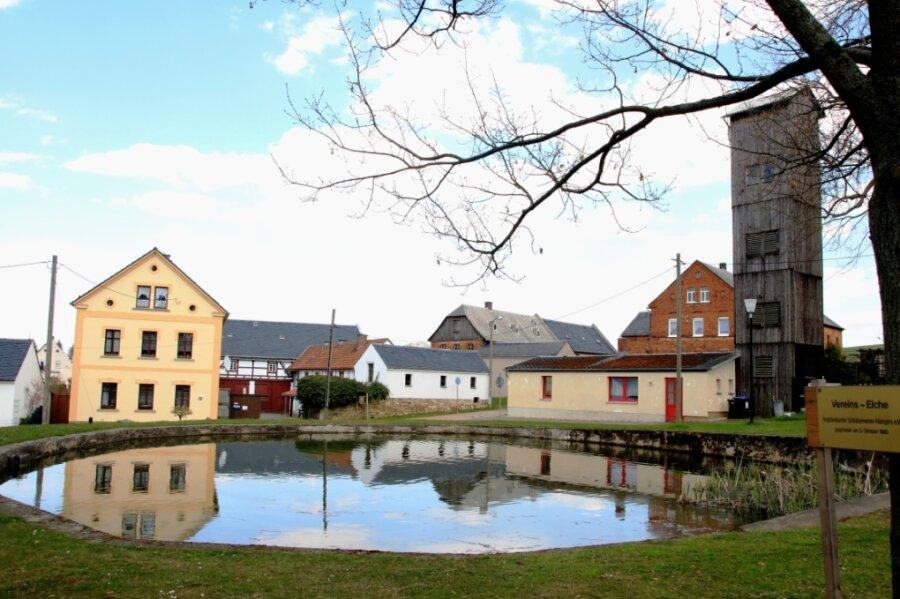 Die Ortsmitte mit Feuerwehrdepot, hölzernem Schlauchturm und Dorfteich.