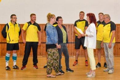 Helen und Griseldis Spitzner von der SG Pfaffengrün (vorn, von links) erhalten von Treuens Bürgermeisterin Andrea Jedzig (EK/CDU), die der Leader-Region Vogtland vorsitzt, den Fördermittelbescheid für die Sporthalle überreicht. Der Verein will neue Tische beschaffen.