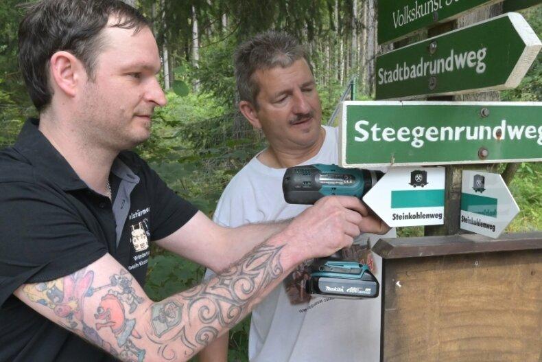 Die Ortswegewarte Tobias Keller (links) und Mike Knobloch bringen im Auftrag der AG Steinkohlenweg derzeit weitere 50 Schilder am gleichnamigen Rad- und Wanderweg an. Die Ergänzung der Beschilderung ist eine Konsequenz aus der aktuellen Analyse durch das Verkehrszentrum.