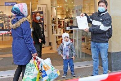 """Seit Dienstag kontrolliert wieder eine Mitarbeiterin des Bekleidungsunternehmens C & A den Einlass im Einkaufszentrum Arcaden. Für """"Click & Meet"""" konnte diese Familie den negativen Cornoatest vorweisen."""