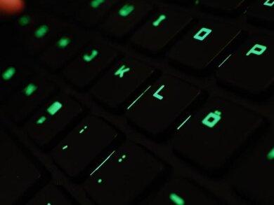 Ein Mann tippt auf einer beleuchteten Tastatur an einem Laptop.