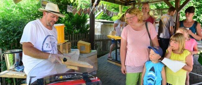 Imker Sandro Farle (l.) führte am Samstag in Hainichen den Besuchern vor, wie Honig geschleudert wird.