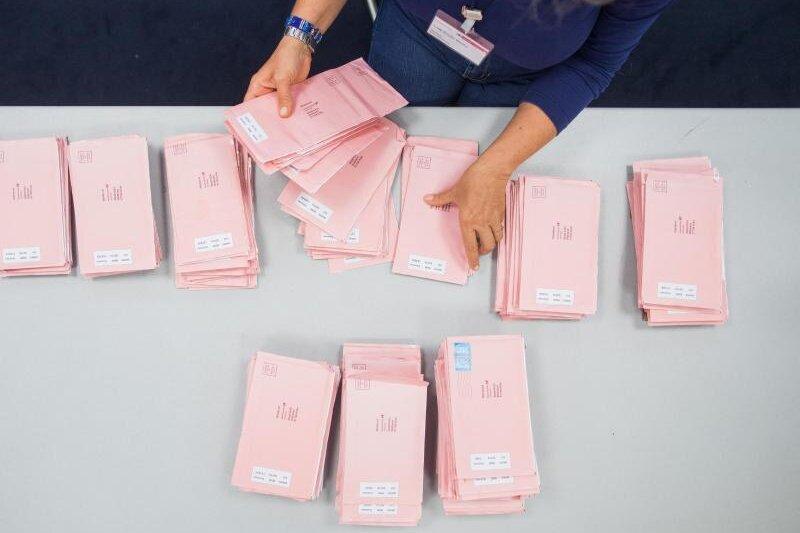Eine Wahlhelferin sortiert Wahlbriefe.