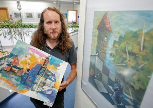 """Mario Schmidt mit dem Bild """"Im wunderlich wilden Wandel der Zeit"""" in der Hand. Das rechte Bild heiß """"Das altbekannte Spiel""""."""