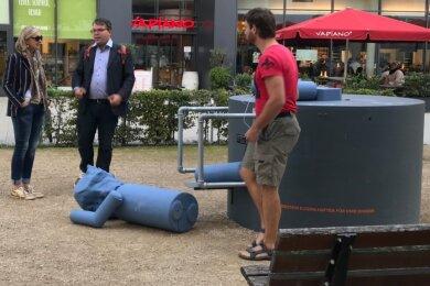"""Die Karl-Marx-Wackelfigur der Künstlerin Else Gabriel liegt auf dem Boden des Johannisplatzes, die Beine sind abgetrennt. Frédéric Bußmann, Leiter der Kunstsammlungen (Bildmitte), schaute sich die Zerstörung des Kunstobjekts, das zur Ausstellung """"Gegenwarten"""" gehört, vor Ort an."""