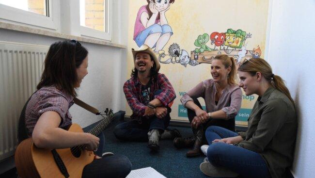Sängerin Stefanie Hertel (2. von rechts) stattete am Freitag mit Tochter Johanna (rechts) und Ehemann Lanny Lanner der Jumi Kinderhilfe in Oelsnitz einen Besuch ab. Loreen Zacher (links), Präventionskursleiterin des Vereins, stellte ein pädagogisches Kinderlied vor.