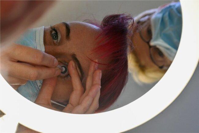 Romy Höher übt unter den Augen von Schwester Angela Hofmann das Einsetzen der Linse.
