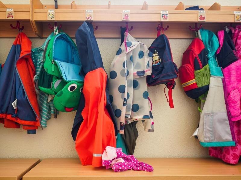 Jacken und Rucksäcke hängen an der Garderobe einer Kita. (Symbolbild).