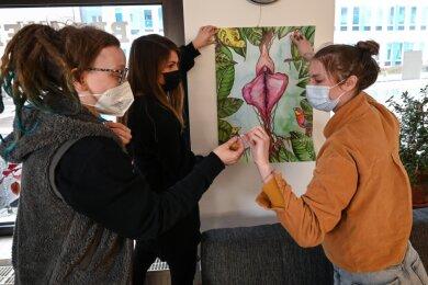 Antje Schulz (links) und Ann-Kristin Balz (Mitte) helfen der Künstlerin Giulietta Scheer beim Anbringen eines ihrer Bilder.