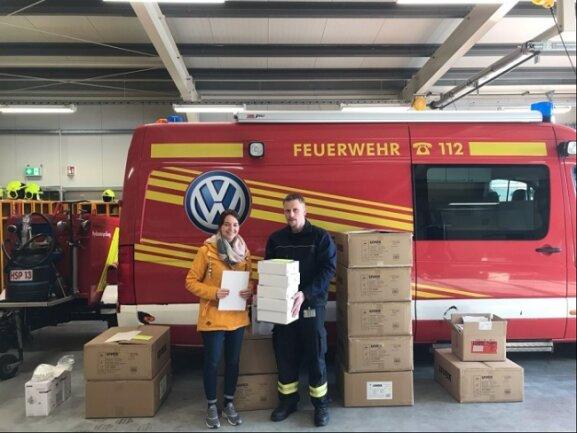 Laura Appelt (l.), Mitarbeiterin der Euro Plus Seniorenbetreuung in Chemnitz, nimmt Atemschutzmasken, Schutzkittel und Schutzbrillen von Werksfeuerwehrmann Thomas Fritzsch auf dem Werksgelände in Zwickau entgegen.
