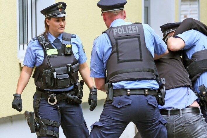 """Hier """"überwältigen"""" die Polizisten in der kleinen Parkanlage ihren Kriminaltechniker. Die Szene ist nachgespielt."""