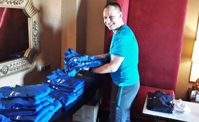 Henry Bütner kümmert sich in einem Hotelzimmer um die Kleidung der Chemnitzer Kicker.