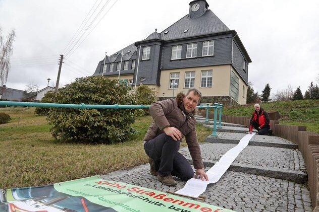 Bürgerinitiative Grünes Band Callenberg Heiko Scheu (vorn) und Rene Engelhardt mit der Unterschriften Rolle vor dem Rathaus in Falken