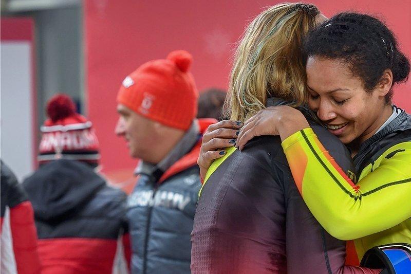 Pilotin Mariama Jamanka (re.) und Anschieberin Lisa Buckwitz umarmen sich im Ziel und feiern ihre Goldmedaille.