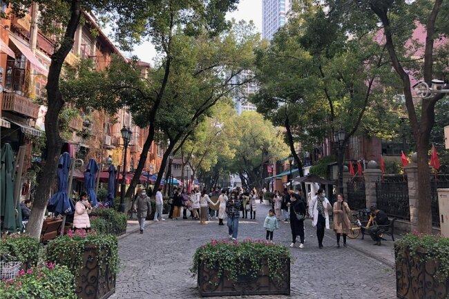 Straßenszene im alten Kolonialviertel der Millionenstadt Wuhan: Die Bewohner des einstigen Corona-Epizentrums haben die Pandemie überwunden und das normale Alltagsleben zieht wieder ein. Die Maske gehört inzwischen zur Normalität.