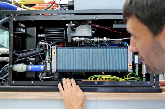 Ein Wissenschaftler der TU Chemnitz bereitet die Brennstoffzelle eines Versuchsfahrzeuges für einen Test vor.