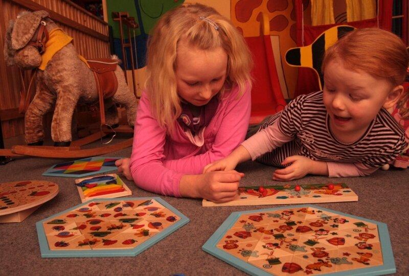 """<p class=""""artikelinhalt"""">Alina (links) und Alia beschäftigen sich im Spielzimmer der Olbernhauer Firma Hess-Holzspielzeug. Neuentwicklungen dieser Steckspiele werden auf der Spielwarenmesse in Nürnberg gezeigt. </p>"""