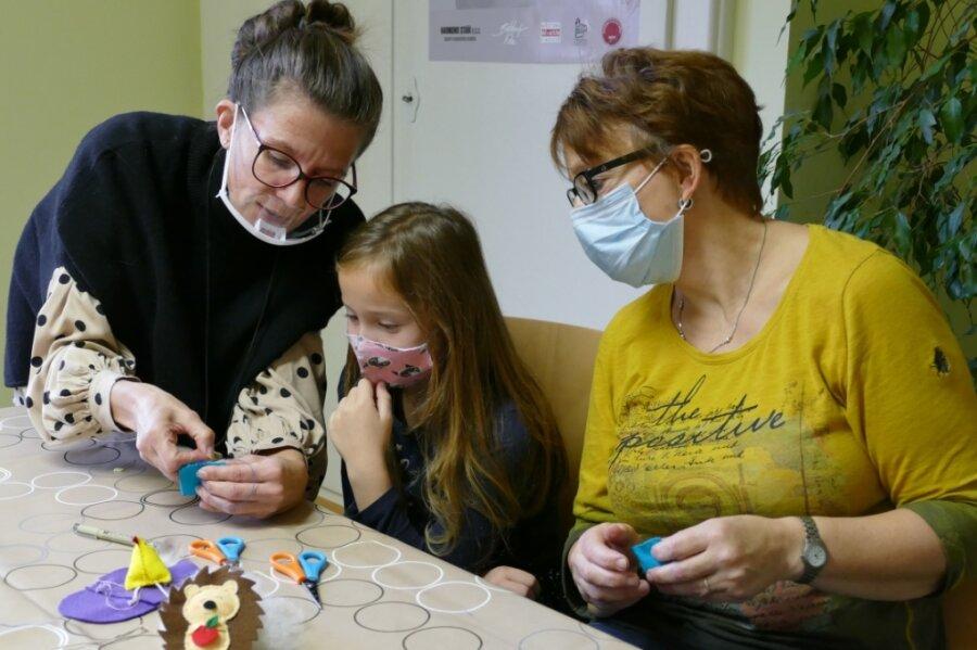 """Ganz genau schauen die Wolkensteinerin Sabine Melzer (r.) und ihre Tochter Leni hin, wie Kursleiterin Sabine Hochmuth alias """"Wollbine"""" die Nadel am Filz ansetzt."""