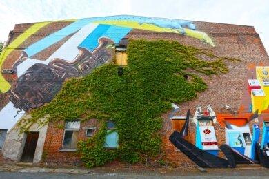 Auf der Ziegelwand der Kulturweberei gestalteten die beiden Künstler ihr Fassadenbild um den Efeu herum.
