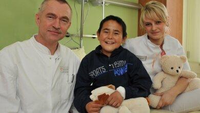 """Ziauddin freut sich, wenn Chefarzt Hubel und Schwester Julia zu ihm kommen. """"Wir haben ihm diese Woche erst mal Spielzeug und Anziehsachen gekauft"""", erzählt Julia Egermann. Sehr gern schaut der Junge auch fern. Den Plüschhund, den er im Arm hat, bekam er von der Röntgenabteilung geschenkt."""